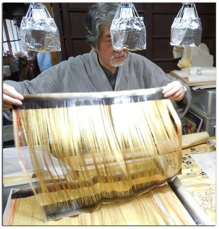 Gold-leaf-artist-showing-cut-gold-leafed-paper-for-weaving